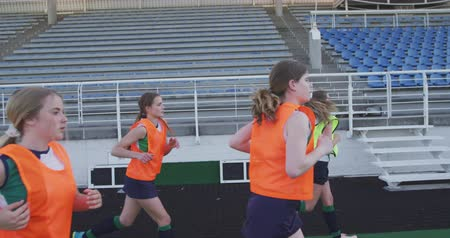 veldhockey : Side view of a team of teenage Caucasian female hockey players, running around the pitch at a stadium in the sun, warming up before playing hockey, slow motion Stockvideo