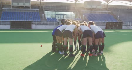 veldhockey : Rear view of a teenage Caucasian female hockey team in a huddle on the pitch at a sports stadium before a hockey match, slow motion Stockvideo