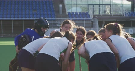 amontoado : Rear view close up of a teenage Caucasian female hockey team in a huddle on the pitch at a sports stadium before a hockey match, slow motion