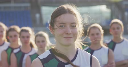 veldhockey : Portrait of a teenage Caucasian female hockey player standing on the pitch at a sports stadium, looking to camera and smiling in the sun, her teammates standing in the background, slow motion