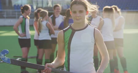 amontoado : Portrait of a teenage Caucasian female hockey player standing on the pitch holding a hockey stick at a sports stadium, looking to camera and smiling in the sun, her teammates standing in the background, slow motion Stock Footage