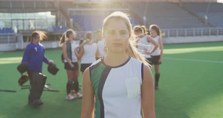 amontoado : Portrait of a teenage Caucasian female hockey player standing on the pitch at a sports stadium, looking to camera and smiling in the sun, her teammates standing in the background, slow motion