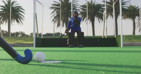 blocage : Low angle side view of a teenage Caucasian female hockey player taking a shot at goal and the goalkeeper blocking the ball, on the pitch at a sports stadium, slow motion