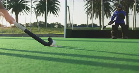 goleiro : Low angle side view of a teenage Caucasian female hockey player taking a shot at goal and scoring against the goalkeeper, on the pitch at a sports stadium, slow motion Stock Footage