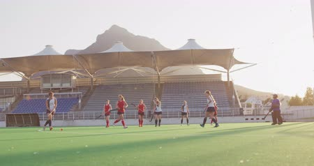 veldhockey : Distant side view of players from two teenage Caucasian female hockey teams in action on the pitch during a hockey match at a sports stadium, slow motion