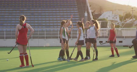 hokej : Side view of players from two teenage Caucasian female hockey teams in action on the pitch during a hockey match at a sports stadium, one team raising their hands and high fiving in celebration of a goal, slow motion