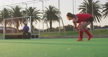 вратарь : Low angle side view of a player from a teenage Caucasian female hockey team in action on the pitch during a hockey match at a sports stadium, taking a shot at goal and scoring agianst the goalkeeper, slow motion Стоковые видеозаписи