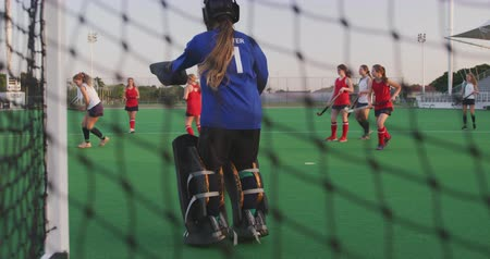 goleiro : Rear view of the goalkeeper of a teenage Caucasian female hockey team in action on the pitch, defending the goal during a hockey match at a sports stadium, slow motion