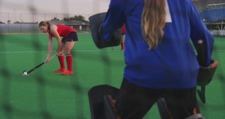 penas : Rear view of the goalkeeper of a teenage Caucasian female hockey team in action on the pitch, defending the goal during a hockey match at a sports stadium, slow motion