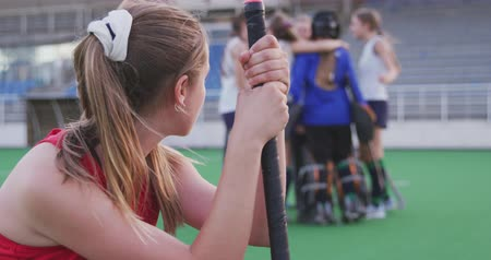 ajoelhado : Side view close up of a teenage Caucasian female hockey player holding her hockey stick and kneeling on the pitch after losing the match, in the background the winning team in a huddle celebrating their victory, slow motion