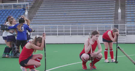 поражение : Side view of a team of teenage Caucasian female hockey players holding their hockey sticks and kneeling on the pitch after losing the match, in the background the winning team in a huddle celebrating their victory, slow motion