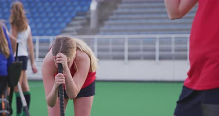 porażka : Side view close up of a teenage Caucasian female hockey player holding her hockey stick and standing on the pitch after losing the match, slow motion Wideo