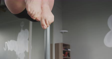 focus pull : Front view close up of a Caucasian woman enjoying pole dance training at a studio, lifting herself of the ground holding the pole, slow motion