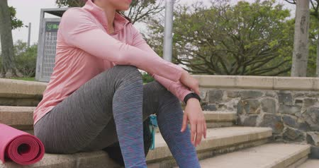 way out : Side view of a Caucasian woman on her way to fitness training, sitting on the steps in a park on a cloudy day, with a yoga mat beside her, slow motion
