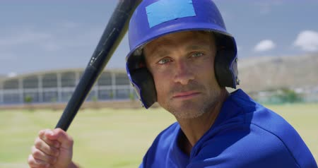 vleermuis : Close up of a Caucasian male baseball player, a hitter, wearing a team uniform and helmet, training at a sports field, holding a baseball bat ready to swing at a pitch in slow motion
