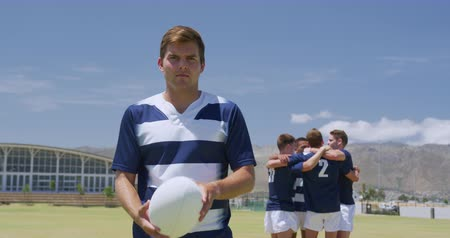 amontoado : Front view of a Caucasian male rugby player holding the ball, with a mixed race group of male teammatesr standing in a huddle behind him, all wearing a team strip, on a rugby pitch before a match, in slow motion Stock Footage