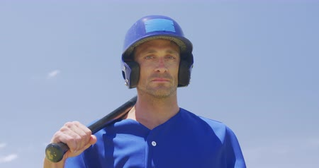 vleermuis : Front view of a Caucasian male baseball player, a hitter, wearing a team uniform and helmet, training at a sports field, holding a baseball bat at a pitch in slow motion