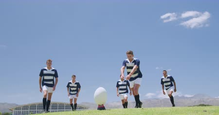 five : Low angle front view of a Caucasian male rugby player kicking a rugby ball, with a group of Caucasian and mixed race male teammates standing behind him, all wearing a team strip, on a rugby pitch during a match, in slow motion
