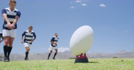 zift : Low angle close up of a Caucasian male rugby player kicking a rugby ball, with a group of Caucasian and mixed race male teammates standing behind him, all wearing a team strip, on a rugby pitch during a match in slow motion Stok Video
