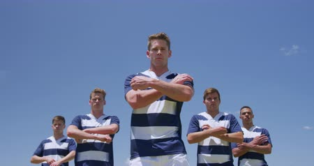 rugby ball : Front view of a group of Caucasian and mixed race male rugby players standing with arms crossed, wearing a team strip, on a rugby pitch before a match, looking straight to camera, in slow motion