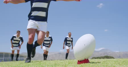flexibilidade : Low angle front view of a Caucasian male rugby player kicking a rugby ball, with a group of Caucasian and mixed race male teammates standing behind him, all wearing a team strip, on a rugby pitch during a match, in slow motion