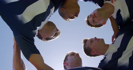 amontoado : Low angle view, looking up at a multi-ethnic group of male rugby players training on a pitch in a motivational huddle, discussing game plan, with arms around shoulders, in slow motion Stock Footage