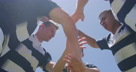 amontoado : Low angle front view of a multi-ethnic group of male rugby players training on a pitch in a motivational huddle, with arms around shoulders and making a hand stack, in slow motion
