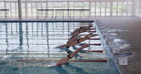 plunging : Side view of multi-ethnic group of male swimmers at swimming pool, jumping from starting blocks, plunging into water in slow motion