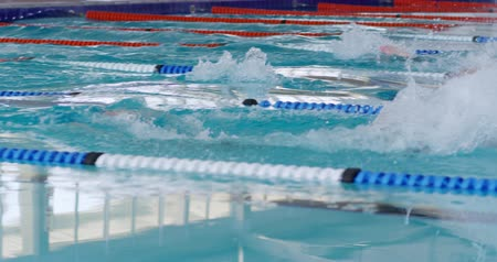 конкурс : Side view of multi-ethnic group of male swimmers at swimming pool, racing each other in lanes, swimming butterfly in slow motion