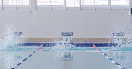 plunging : Front view of multi-ethnic group of male swimmers at swimming pool, jumping from starting blocks, plunging into water in slow motion