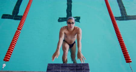 plunging : Front view of Caucasian male swimmer at swimming pool, starting backstroke in the pool, plunging into water, swimming backstroke in slow motion Stock Footage