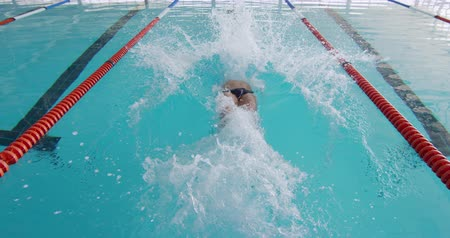nadador : Front view of Caucasian male swimmer at swimming pool, starting backstroke in the pool, plunging into water, swimming backstroke in slow motion Stock Footage
