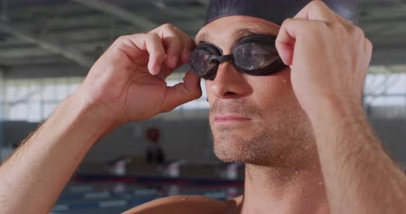 plavec : Side view close up of serious Caucasian male swimmer at swimming pool, putting on his pool goggles, wearing swimming cap, in slow motion