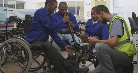undefined : Side view of a group of African American male workers and a Caucasian male supervisor in a workshop at a factory making wheelchairs, inspecting a product, the supervisor kneeling and writing on a clipbaord a clipboard, one of the workers is disabled and s