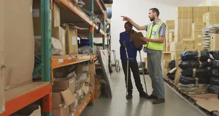 kule : Side view of an African American male worker and a Caucasian male supervisor in a storage warehouse at a factory making wheelchairs, standing and inspecting storage shelves, the supervisor writing on a clipboard, his colleague is standing on crutches Ã