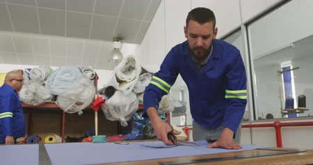 verimlilik : Front view of a Caucasian male worker in a workshop at a factory making wheelchairs, standing at a workbench, cutting material with scissors, a coworker walking behnd him, in slow motion