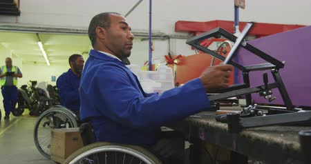 kule : Side view of two disabled African American male workers in a workshop at a factory making wheelchairs, sitting at a workbench assembling parts of a product, both in a wheelchairs, with coworkers walking past in the background, one on crutches