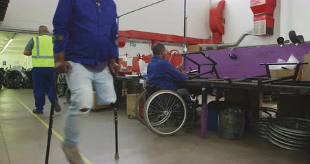 kule : Side view of two disabled African American male workers in a workshop at a factory making wheelchairs, sitting at a workbench assembling parts of a product, sitting in wheelchairs, whiel coworkers walk past, one on crutches