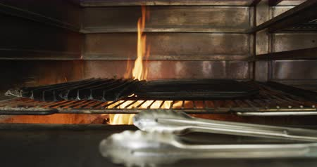 tang : Close up of flames in a grill in a busy restaurant kitchen, tongs and frying trays prepared. Busy chefs at work in commercial kitchen.