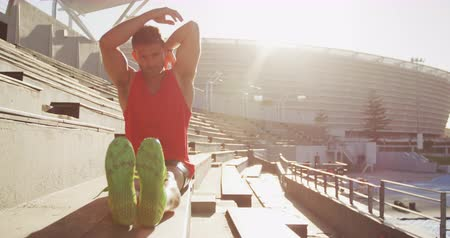 músculos : Front view of a Caucasian male athlete practicing at a sports stadium, stretching arms and legs, slow motion. Track and Field Sports Training in Stadium.