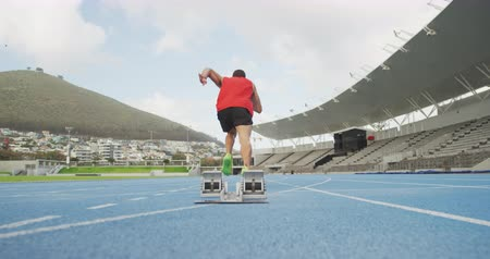 começando : Rear view of a Caucasian male athlete practicing at a sports stadium, starting sprinting from running blocks, slow motion. Track and Field Sports Training in Stadium.