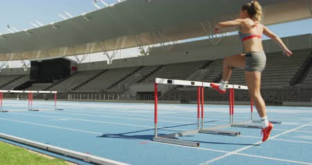 felnőtt : Rear view of a Caucasian female athlete practicing at a sports stadium, hurdling on running track, slow motion. Track and Field Sports Training in Stadium.