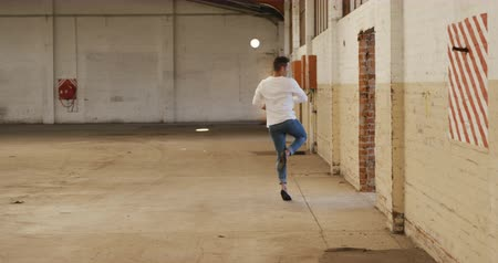 chaussures ballerines : Front view of a Caucasian male ballet dancer practicing in an empty warehouse, dancing and turning, slow motion. Cool Generation Z hipster style concept. Vidéos Libres De Droits