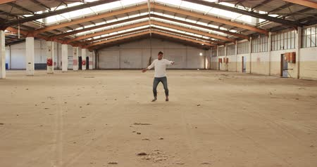 навыки : Front view of a Caucasian male ballet dancer practicing in an empty warehouse, dancing and turning, slow motion. Cool Generation Z hipster style concept. Стоковые видеозаписи