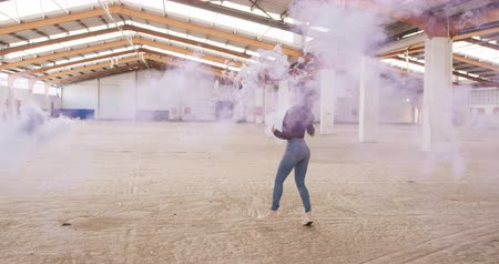 grenade : Side view of mixed race female dancer in an empty warehouse, running and holding smoke grenade, slow motion. Cool Generation Z hipster style concept. Stock Footage