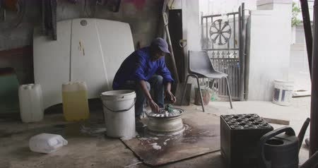 alaşım : Front view of a senior African male panel beater in a township workshop, cleaning an alloy wheel, slow motion. Shot in Capetown South Africa.