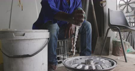 alaşım : Front view of an African male panel beater in a township workshop, cleaning an alloy wheel, slow motion. Shot in Capetown South Africa. Stok Video