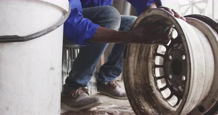 cape wheel : Front view of a senior African male panel beater in a township workshop, cleaning an alloy wheel. Shot in Capetown South Africa. Stock Footage