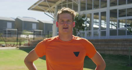 orange t shirt : Portrait of a Caucasian male runner wearing an orange t shirt training at a sports field, standing and resting after training, looking to camera and smiling. Track and Field Sports Training in Stadium, in slow motion