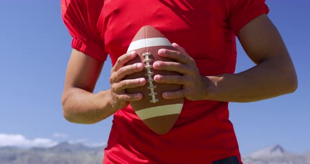 flexibilidade : Front view mid section of a mixed-raced American football player holding a ball in both hands at a sports field, in front of blue sky, in slow motion. Track and Field Sports Training in Stadium.